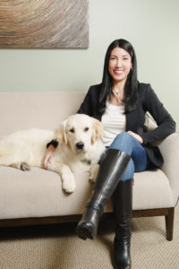 Child Psychiatrist Beth Ballen, MD, posing for a portrait inside her office with our therapy dog Webster.