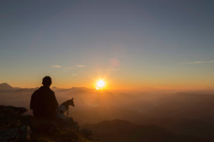 Man Reflecting At Sunset With Dog